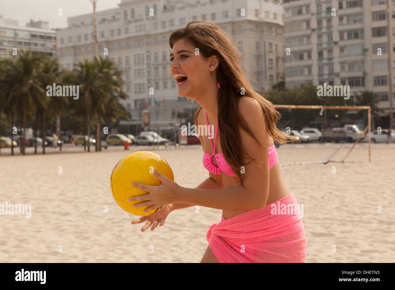 Young woman holding yellow beach ball, Copacabana Beach, Rio De Janeiro, Brazil - Stock Image