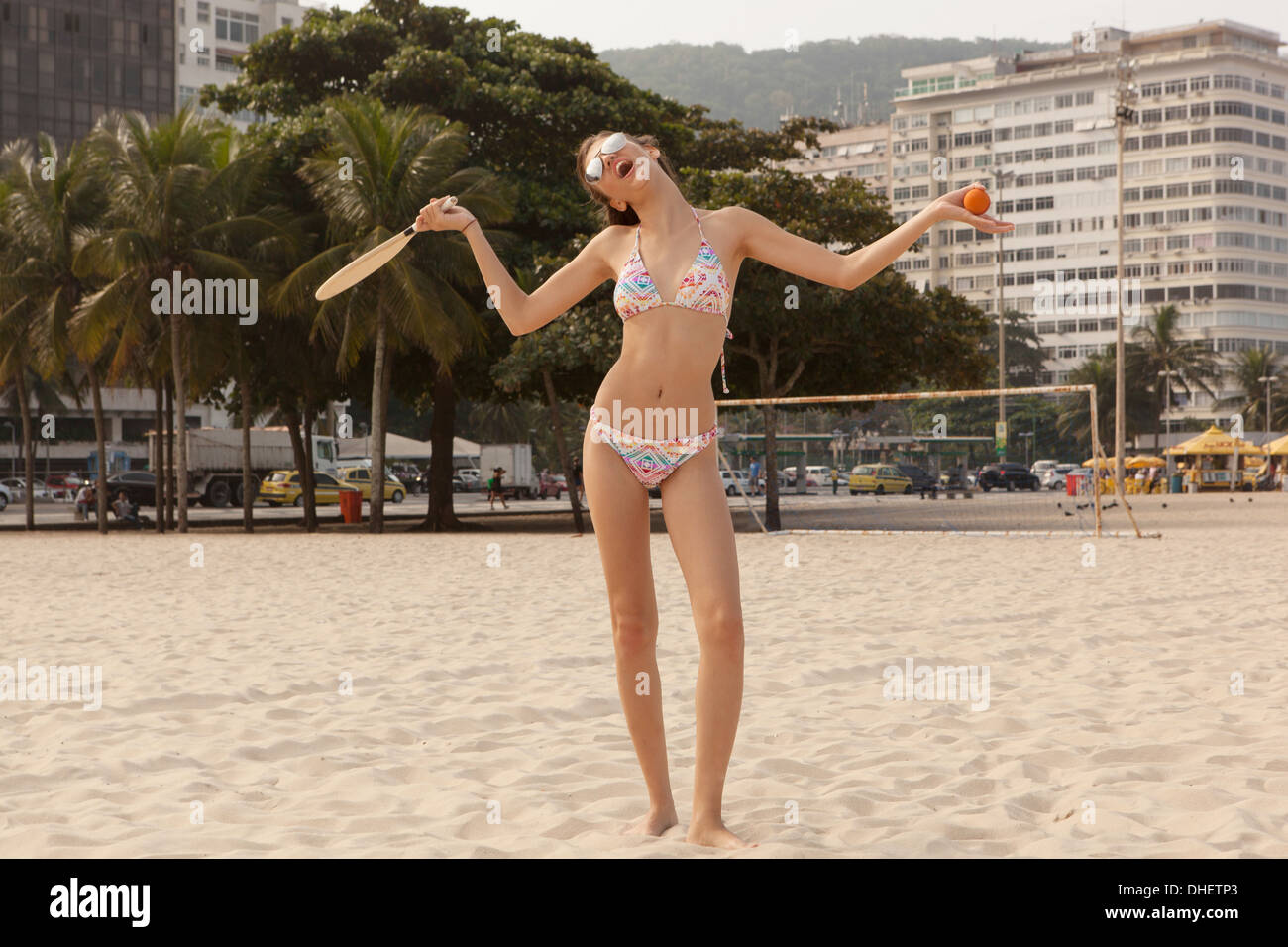 Woman standing with funny gesture on Copcacabana Beach, Rio de Janeiro, Brazil - Stock Image