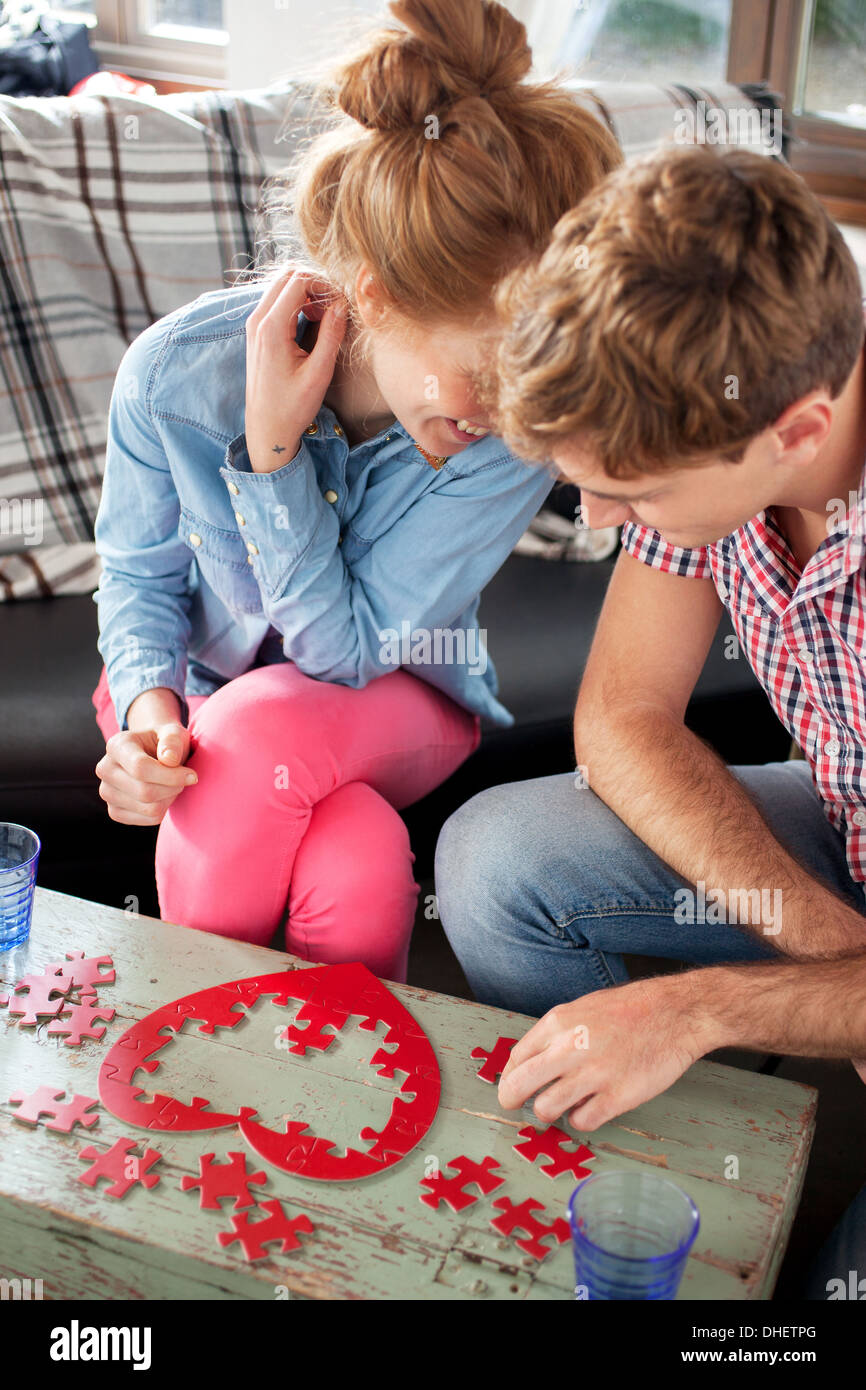 Couple doing heart shaped jigsaw - Stock Image