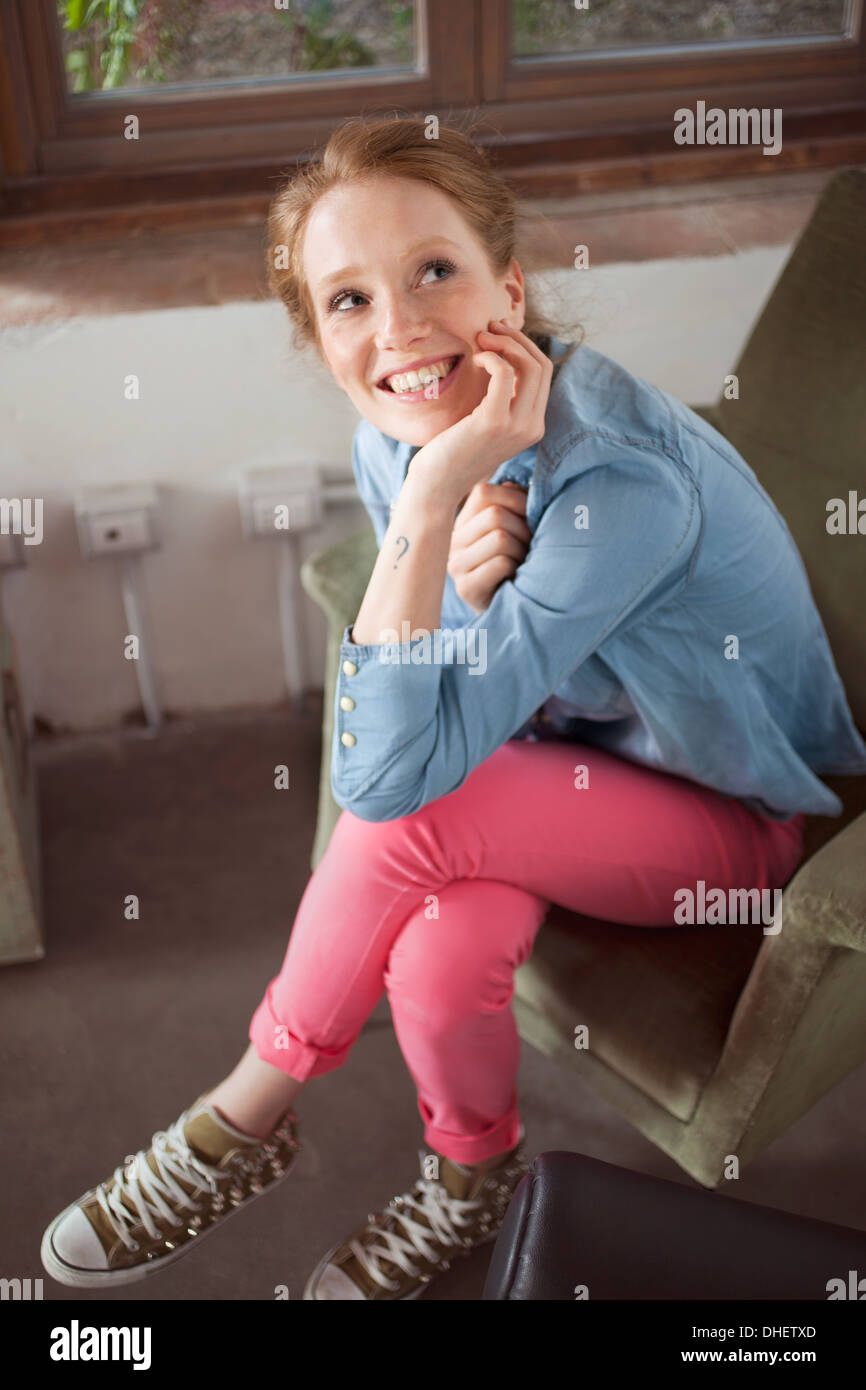 Young woman sitting with legs crossed Stock Photo