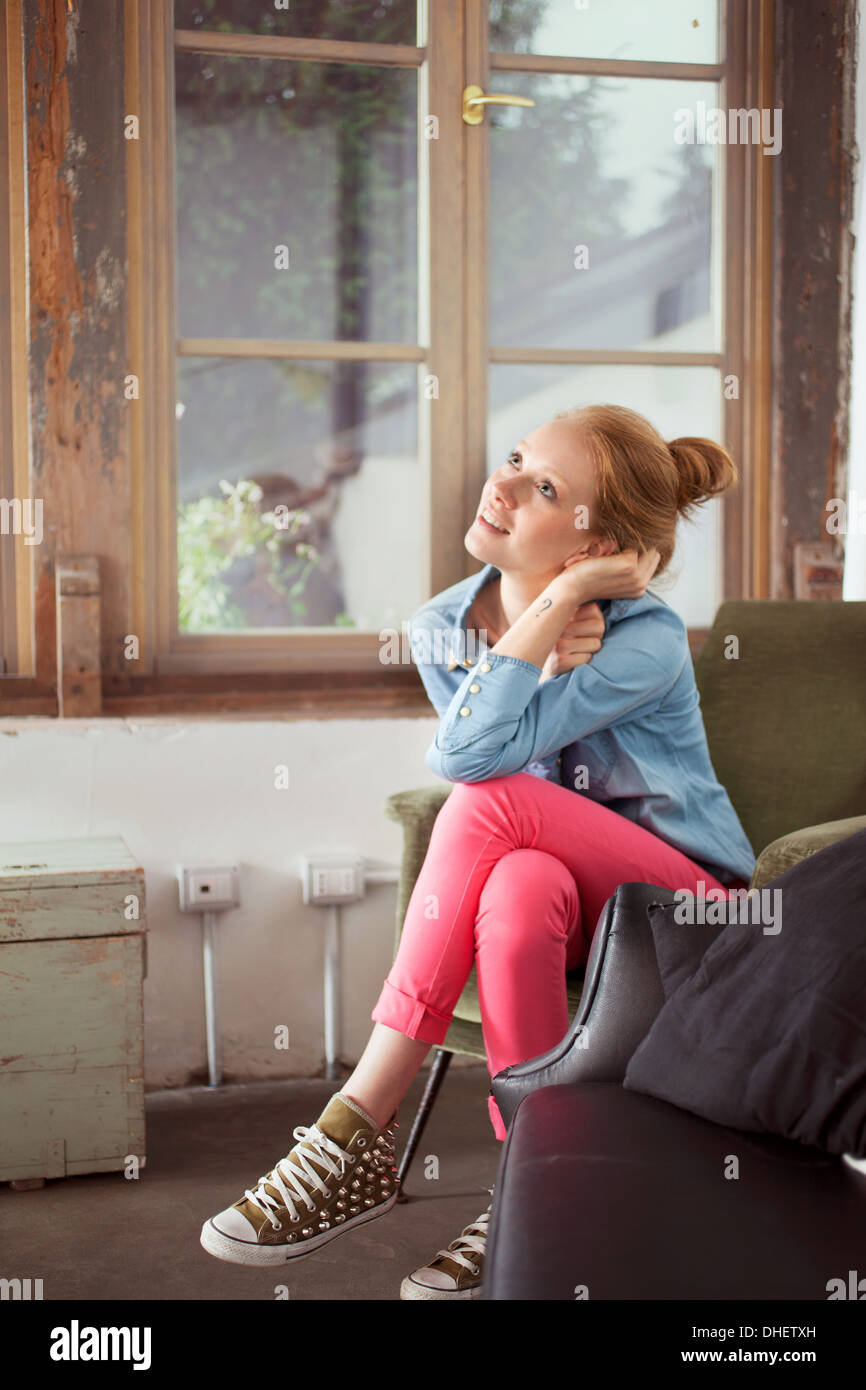 Young woman sitting with legs crossed - Stock Image