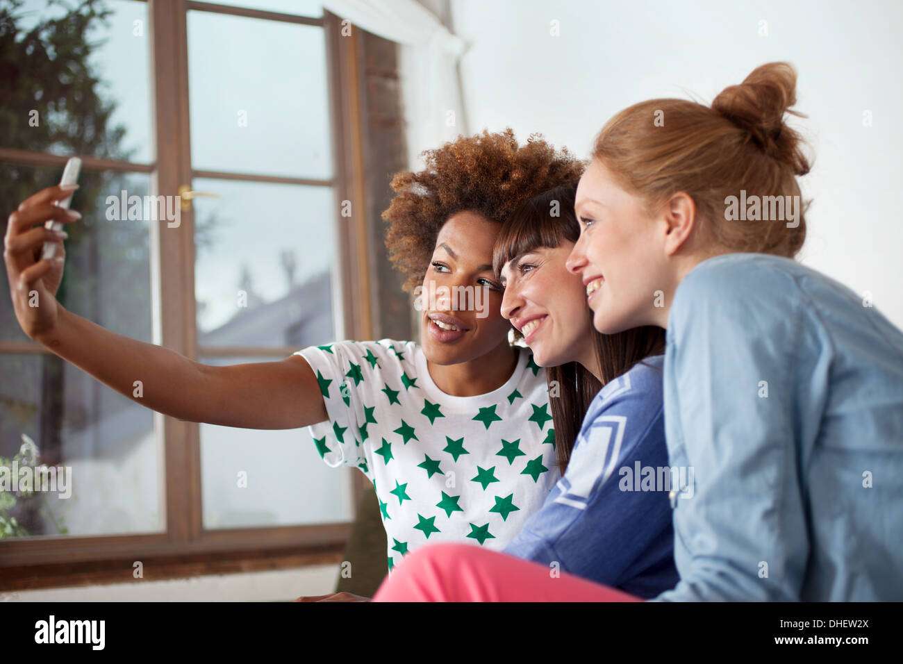 Three female friends photographing themselves with camera phone Stock Photo