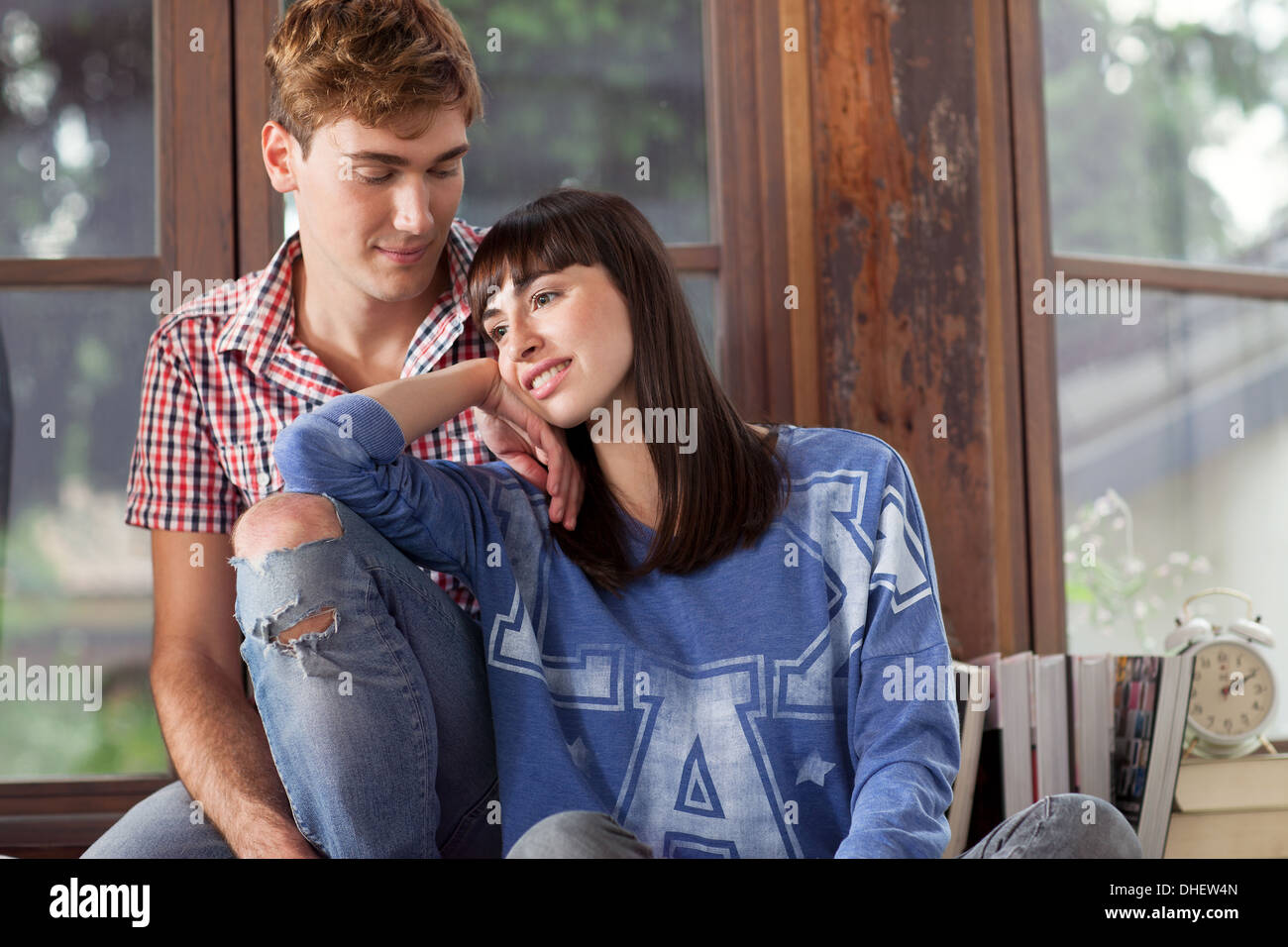 Portrait of couple, woman leaning on man's knee - Stock Image