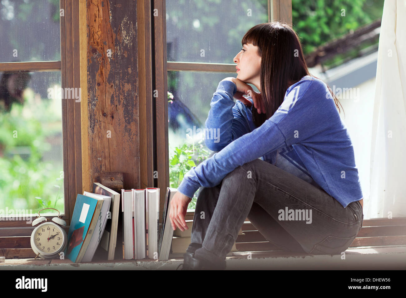 Woman sitting on windowsill - Stock Image