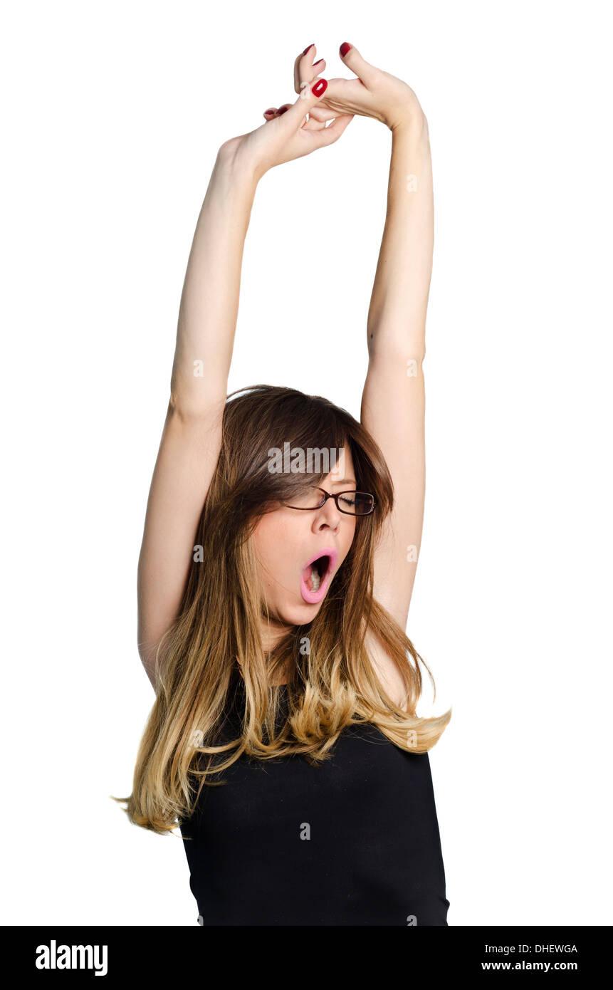 Brunette girl yawning and stretching isolated on white background - Stock Image
