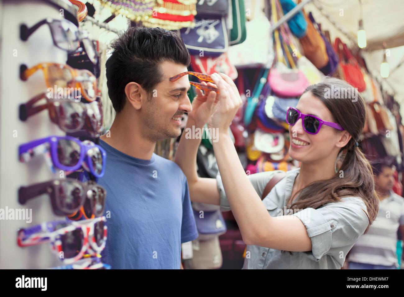 Young couple trying on sunglasses, San Lorenzo market, Florence, Tuscany, Italy - Stock Image