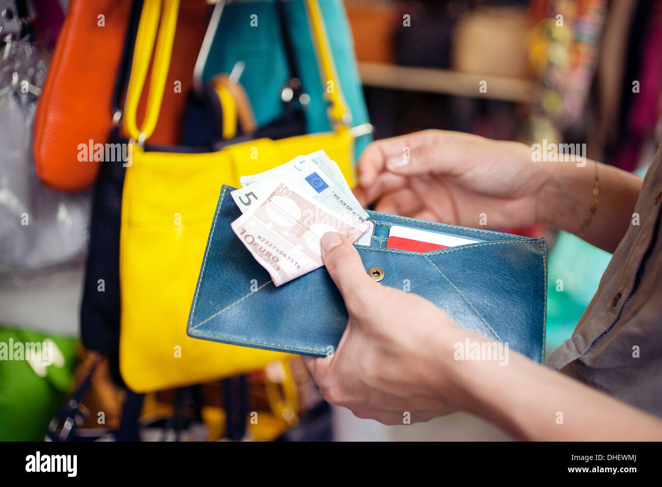 Young woman buying handbag, San Lorenzo market, Florence, Tuscany, Italy - Stock Image