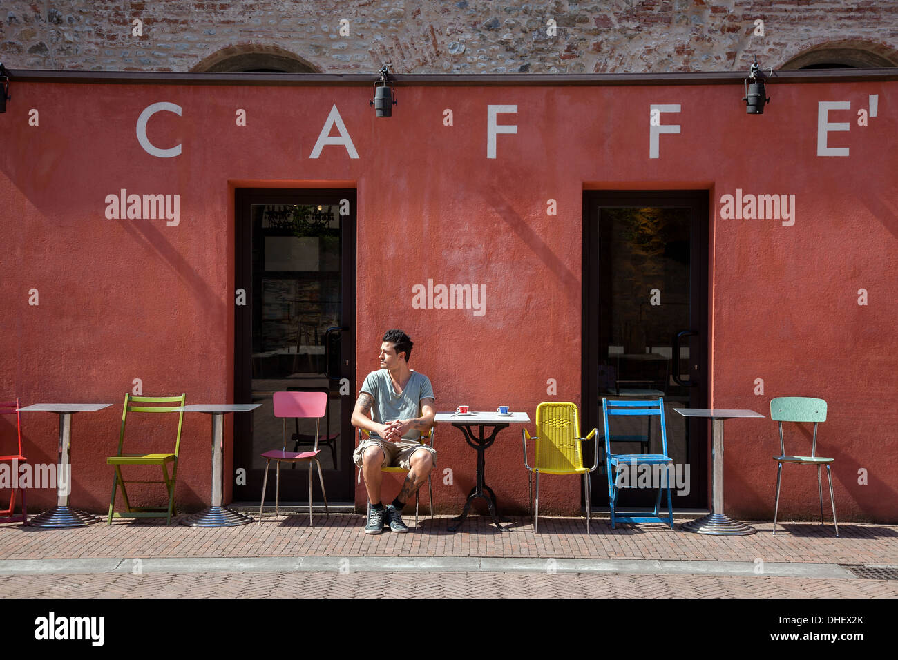 Young man sitting outside cafe, Florence, Tuscany, Italy - Stock Image