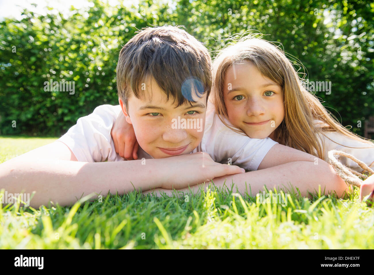 Portrait of brother and sister lying on grass - Stock Image