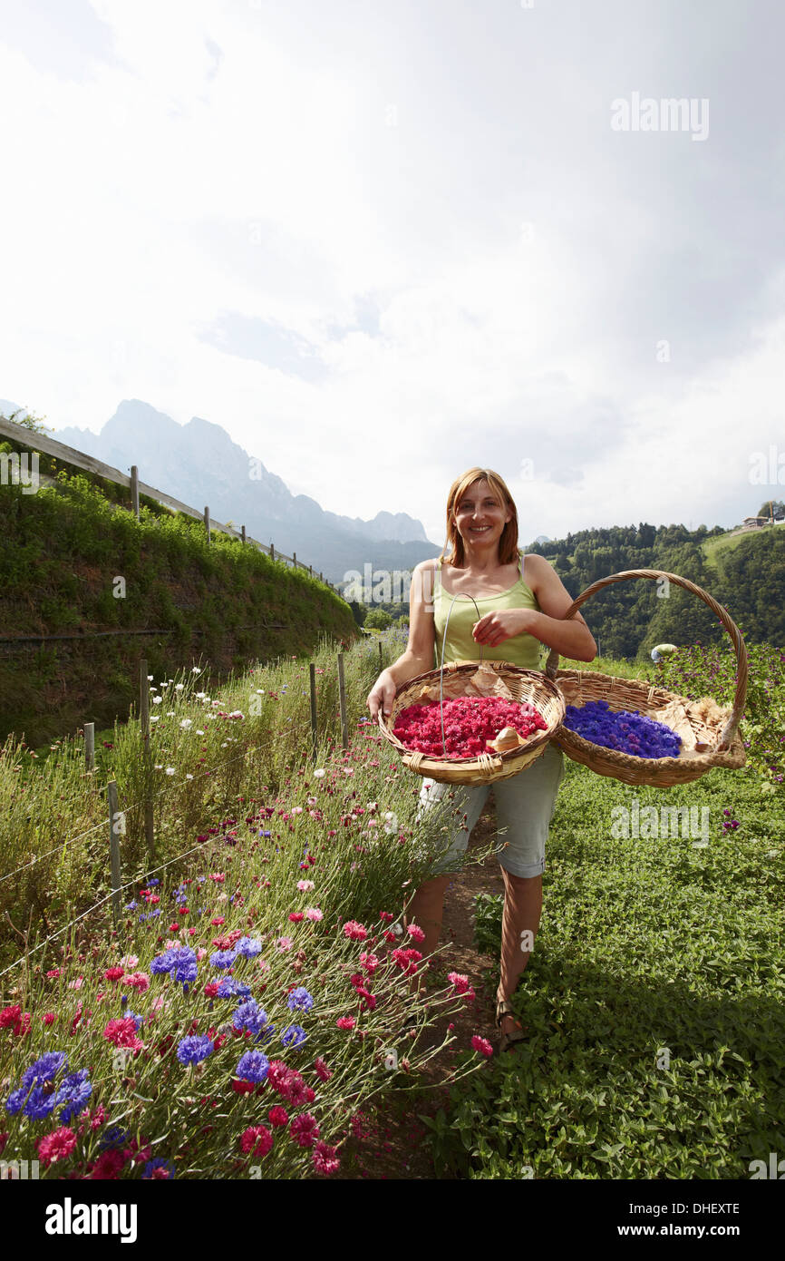 Woman with two baskets of flowers - Stock Image