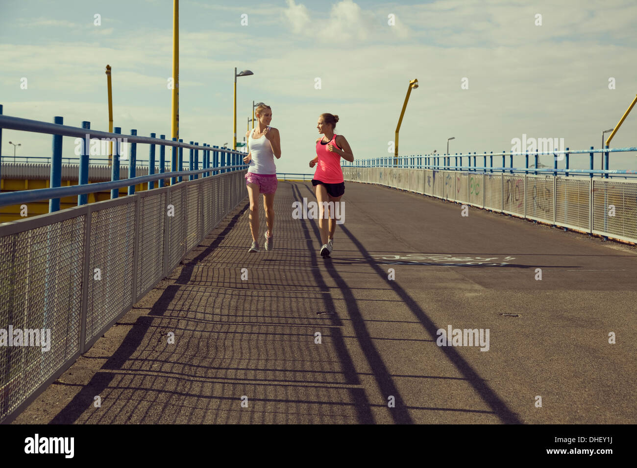 Young female joggers running on bridge - Stock Image