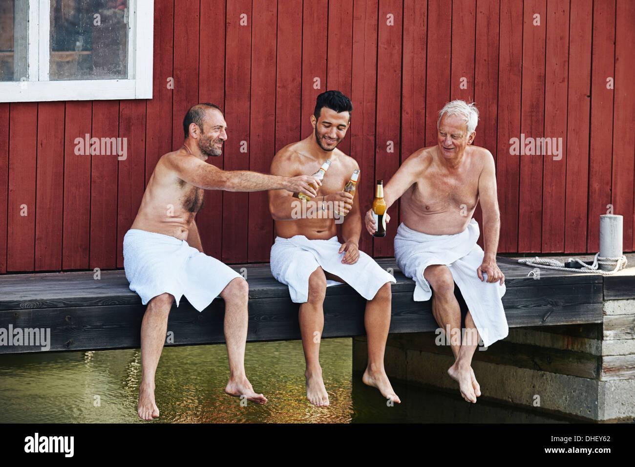 Three men sharing a beer outside sauna - Stock Image