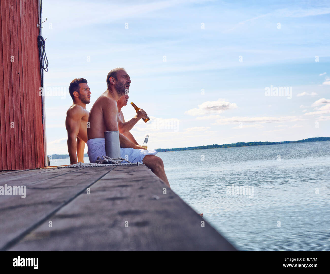 Three male friends sitting outside sauna enjoying beer - Stock Image
