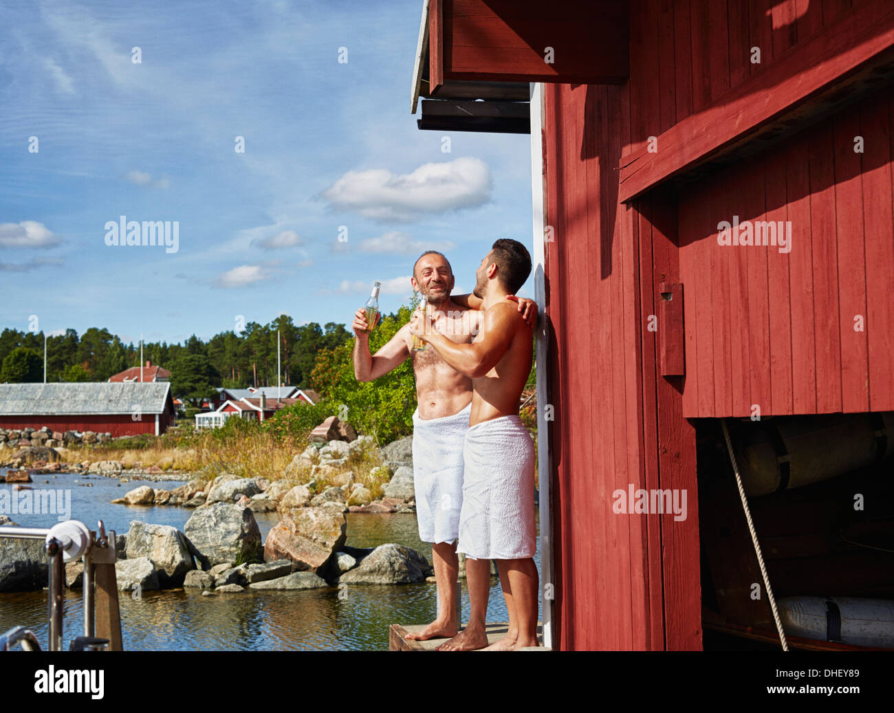 Two men with beers outside sauna - Stock Image