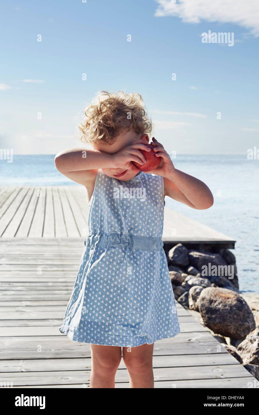 Portrait of female toddler with red apple, Utvalnas, Gavle, Sweden - Stock Image