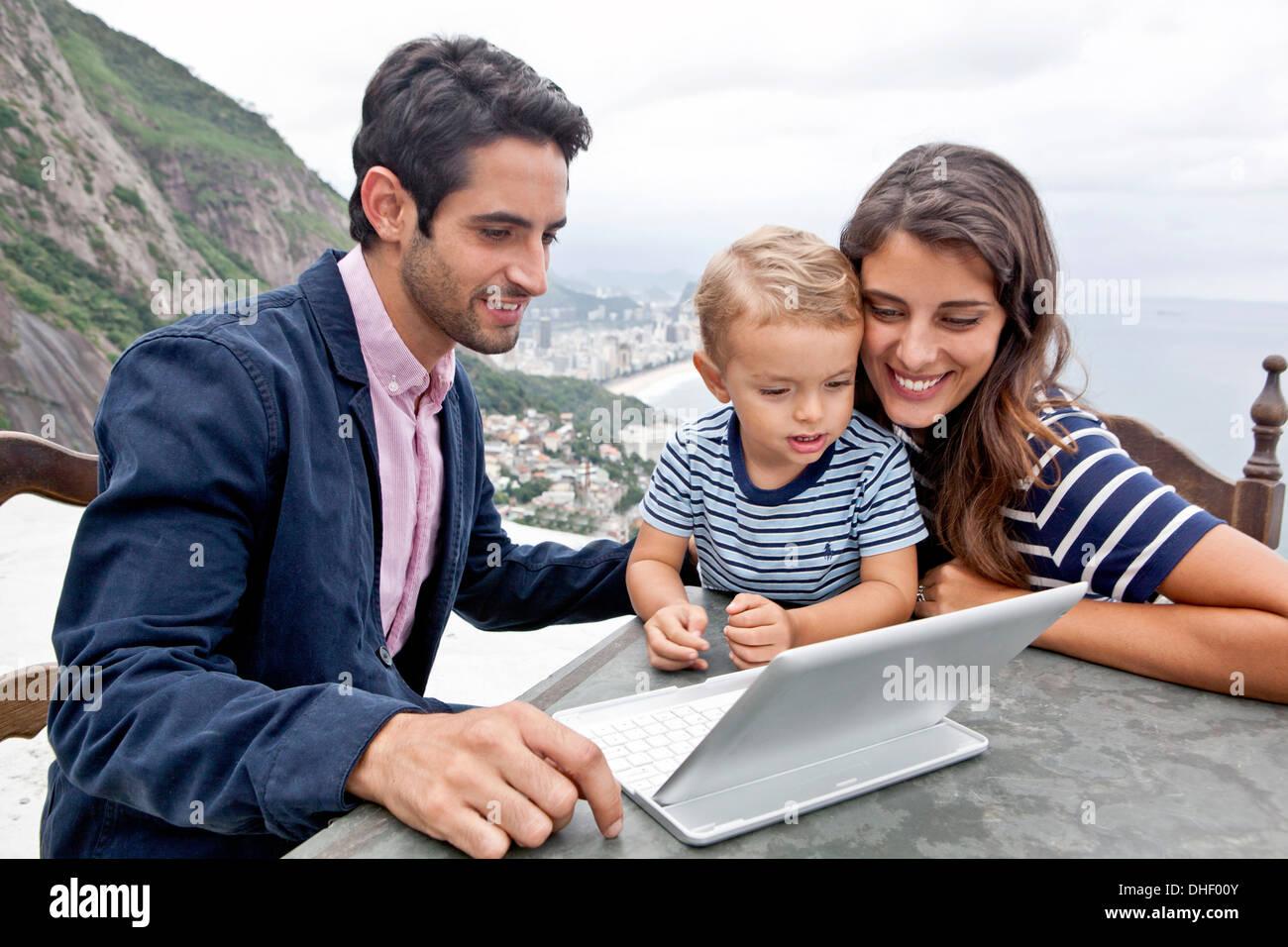 Young family with laptop, Casa Alto Vidigal, Rio De Janeiro, Brazil - Stock Image