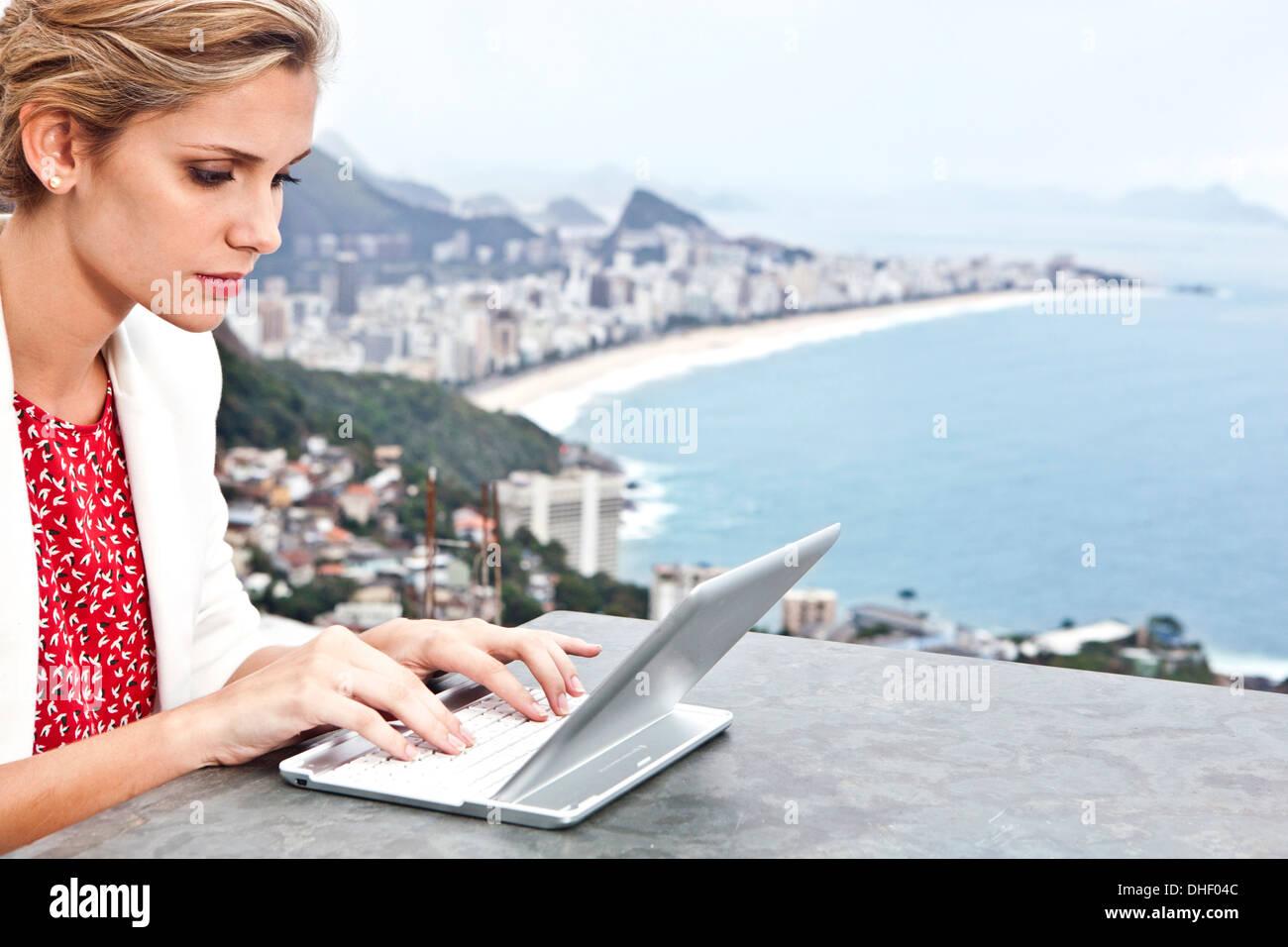 Young woman using laptop, Casa Alto Vidigal, Rio De Janeiro, Brazil - Stock Image