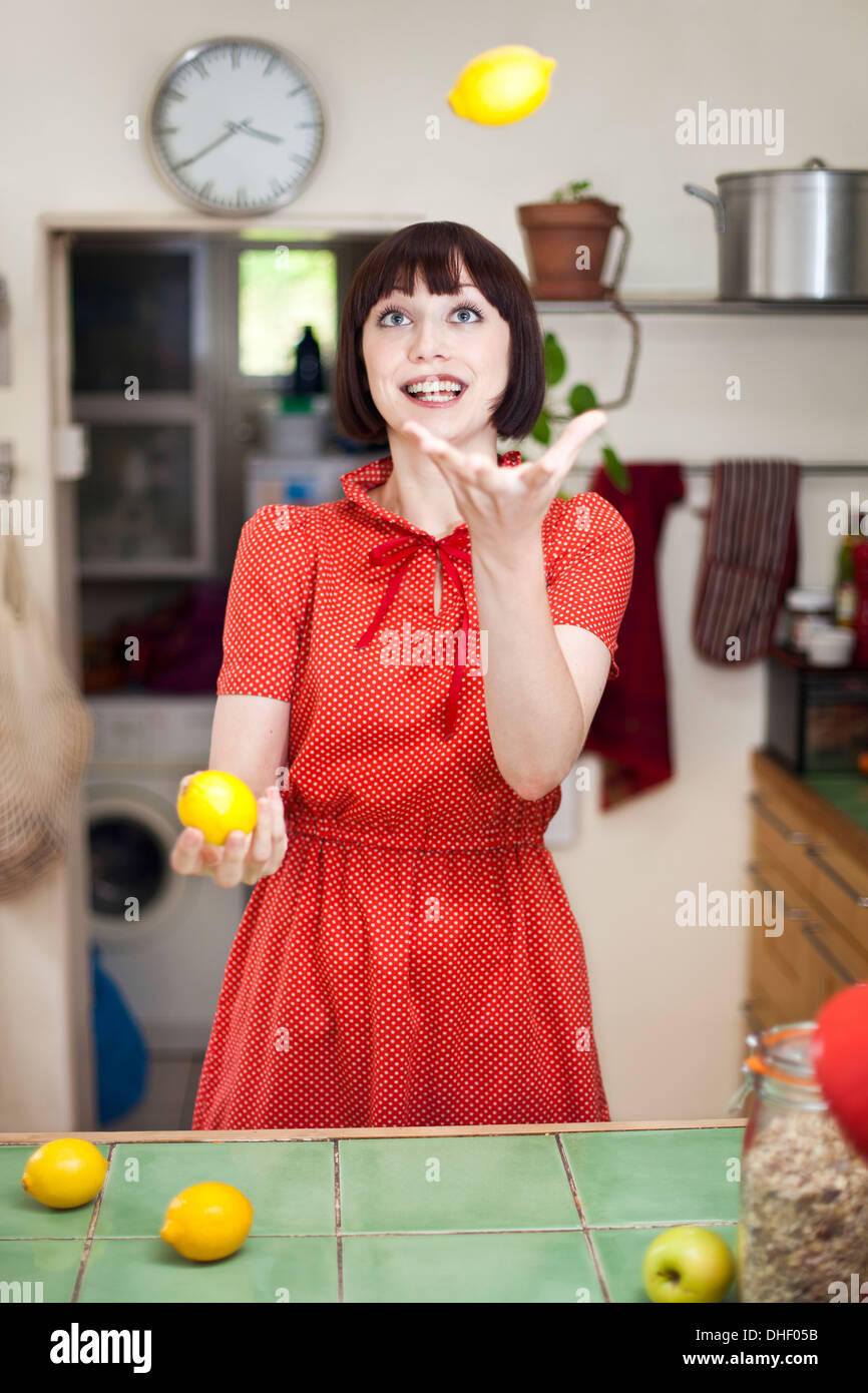Young woman in kitchen juggling lemons - Stock Image
