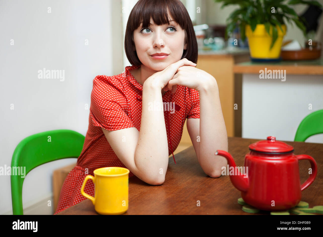 Portrait of young woman sitting at kitchen table - Stock Image