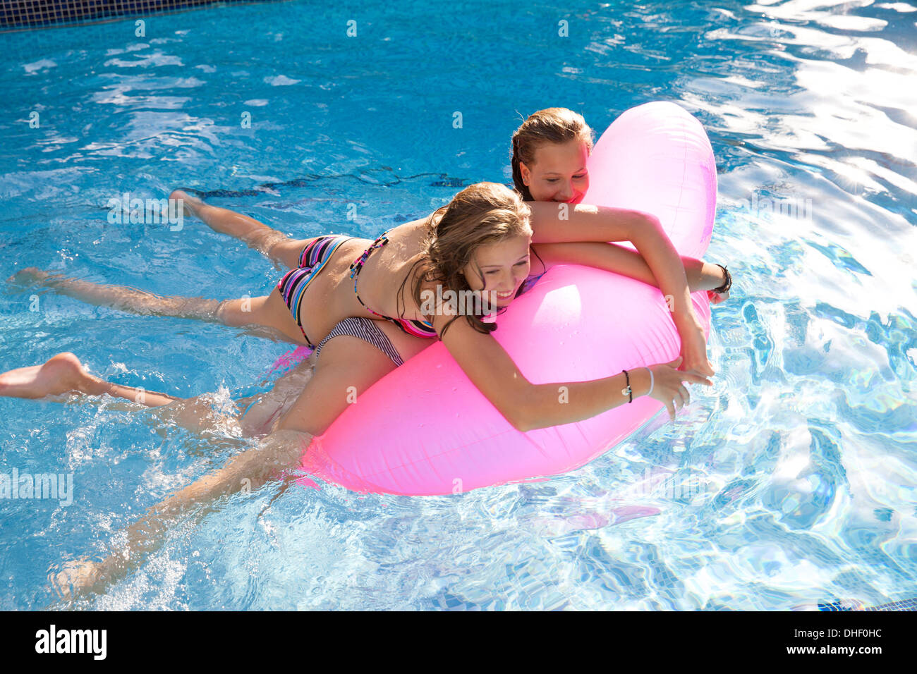 Two teenage girls holding onto air bed in swimming pool - Stock Image