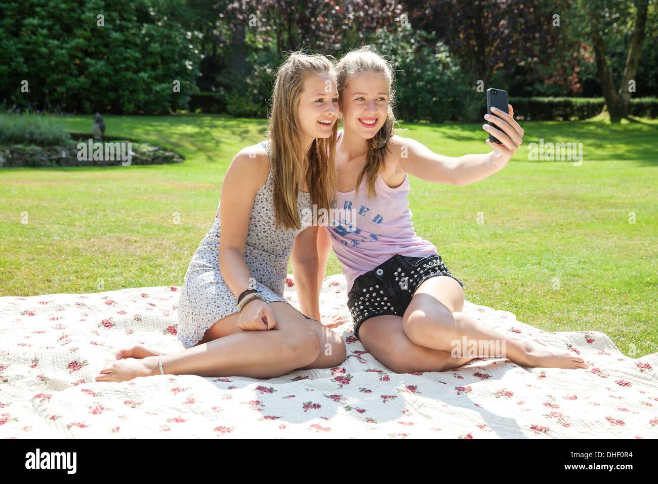 Two teenage girls on picnic blanket taking self portrait - Stock Image
