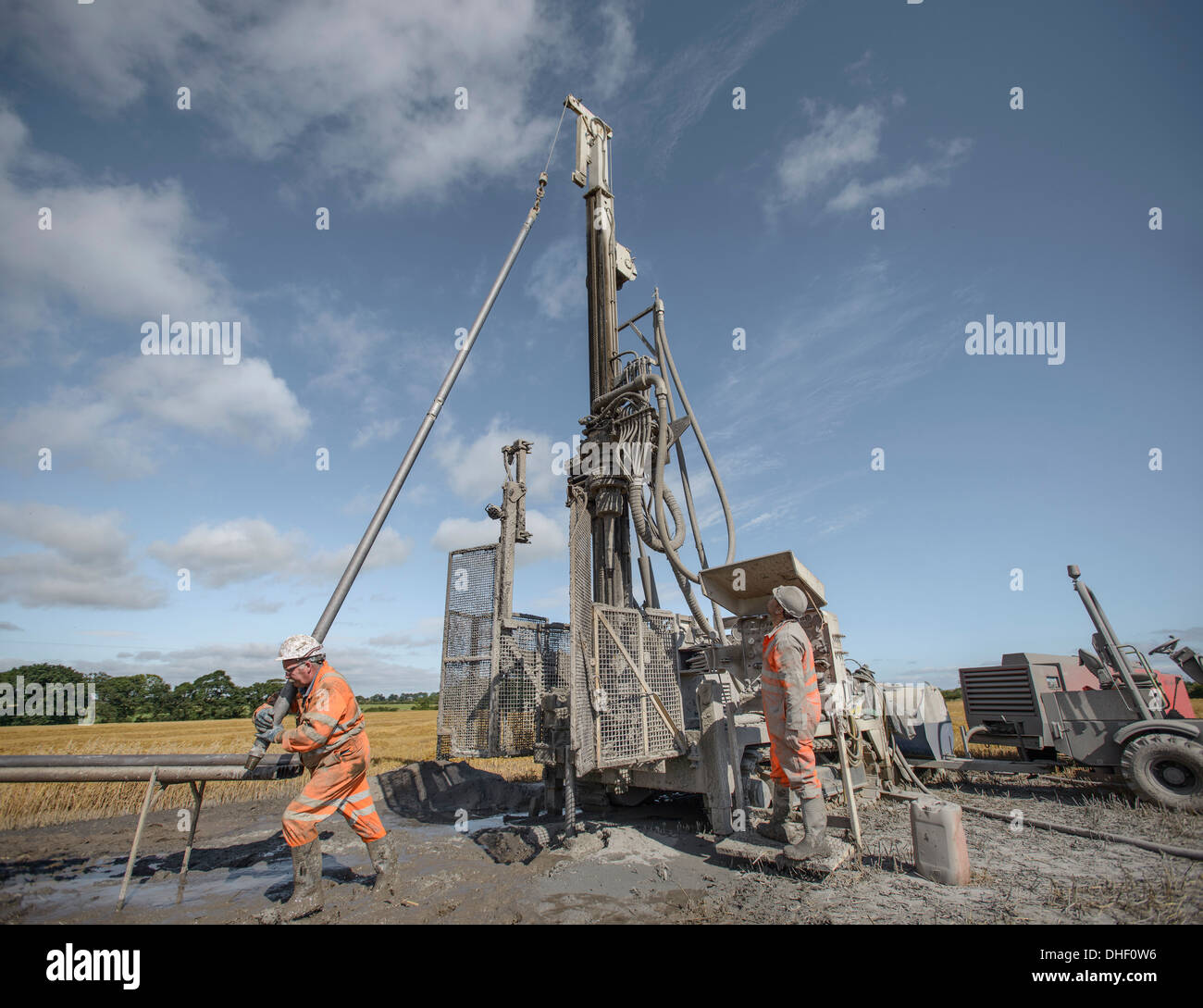 Workers operating drilling rig to explore for coal in field - Stock Image