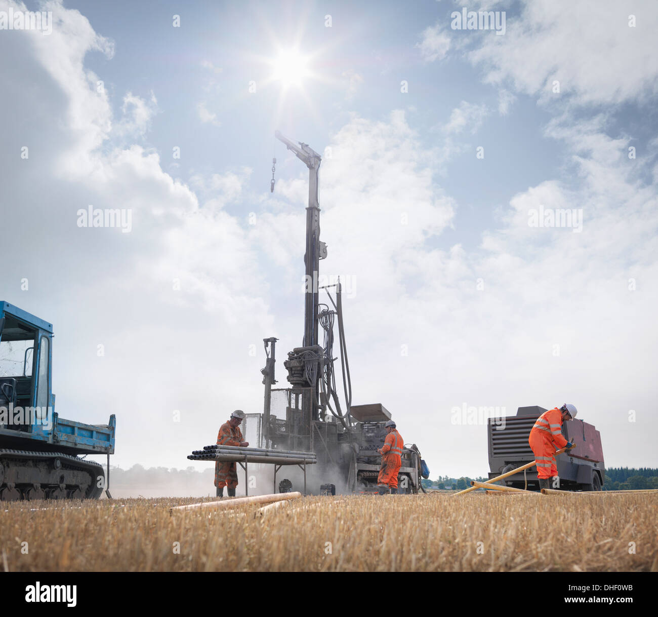 Workers and drilling rig exploring for coal in field - Stock Image