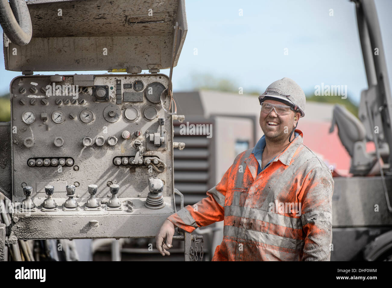 Drilling rig worker in hard hat and workwear, smiling - Stock Image