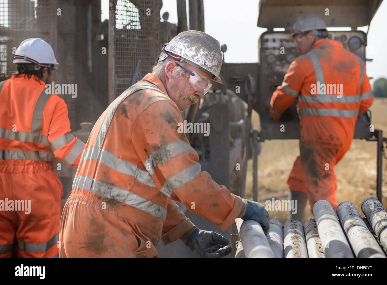 Workers in hard hats operating drilling rig - Stock Image