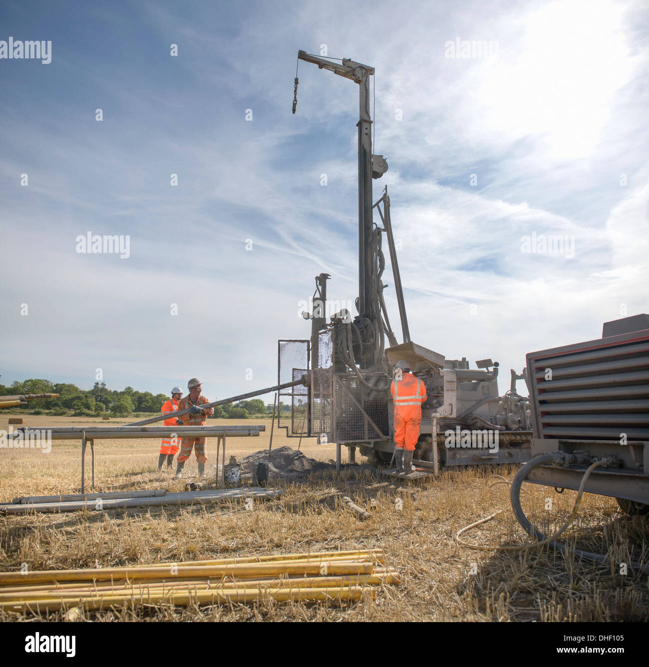Small team of workers operating drilling rig in field - Stock Image