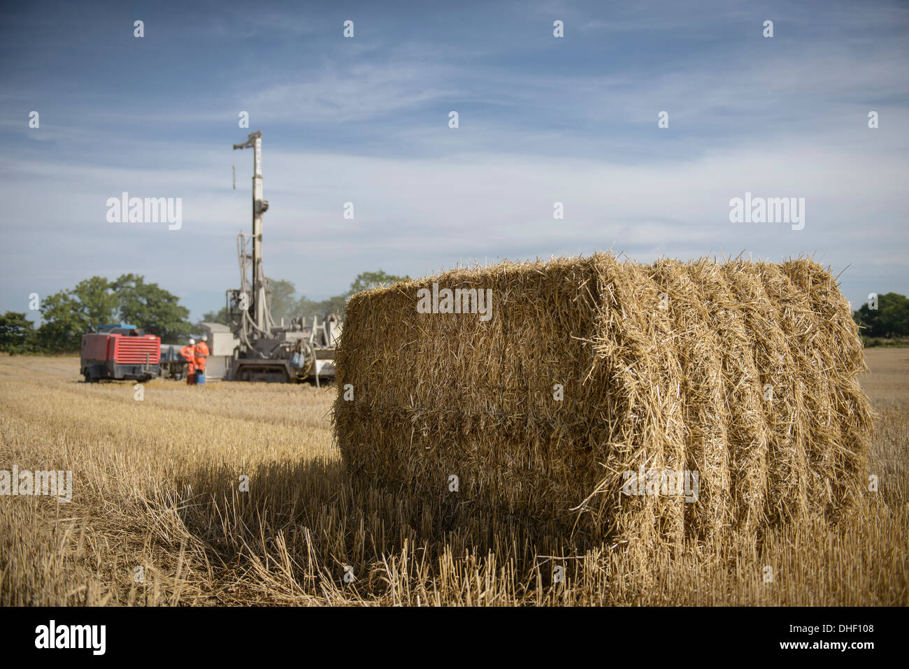 Drilling rig in field with hay bale in foreground - Stock Image
