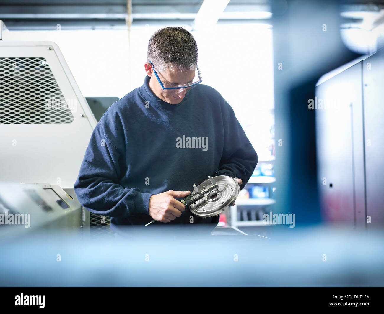Engineer measuring metal part in factory - Stock Image