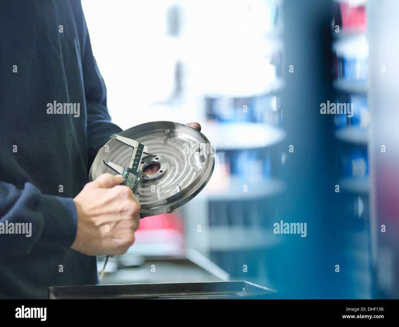 Engineer measuring metal part in factory, close up - Stock Image