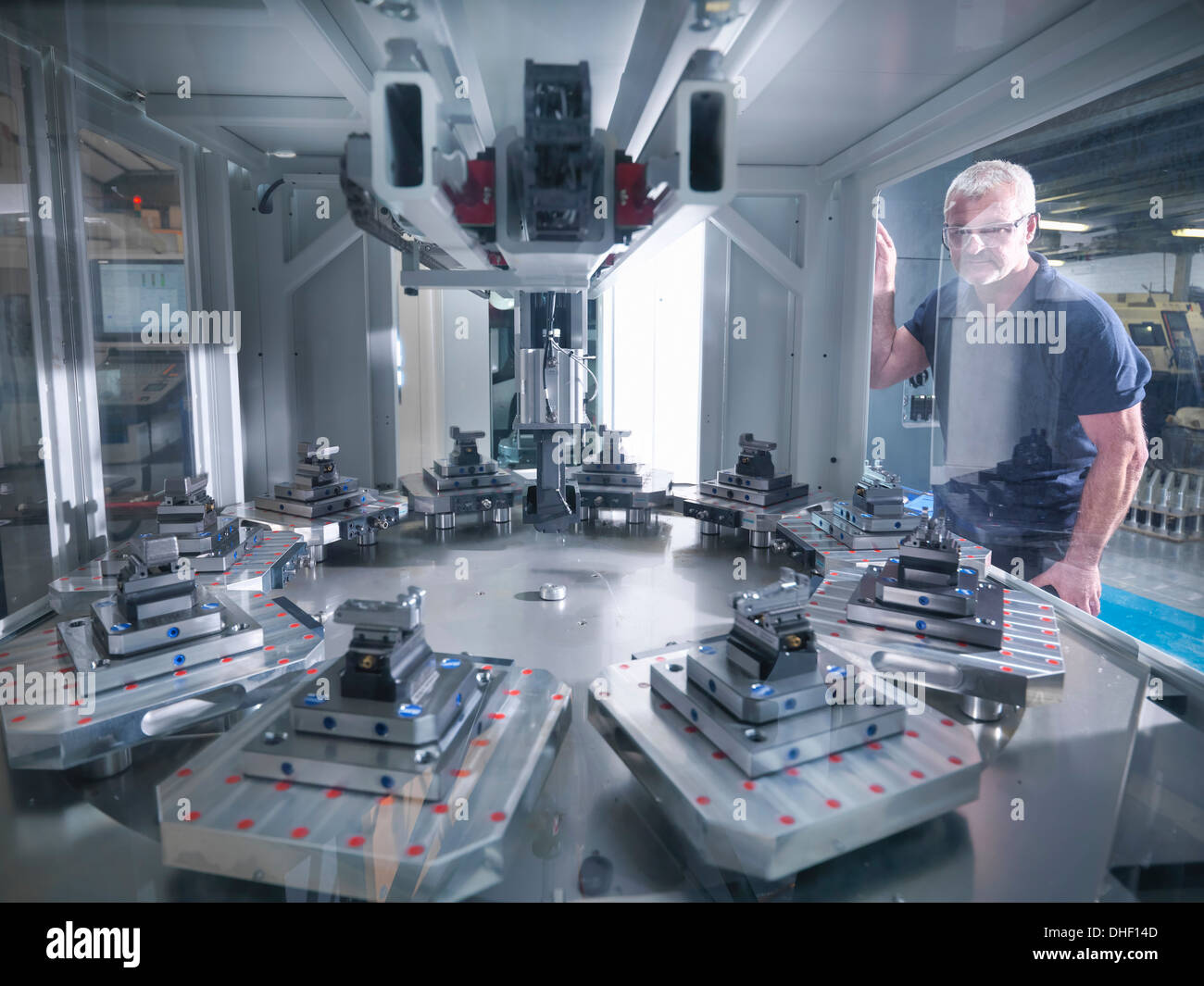 Engineer inspecting automatic lathe in factory - Stock Image