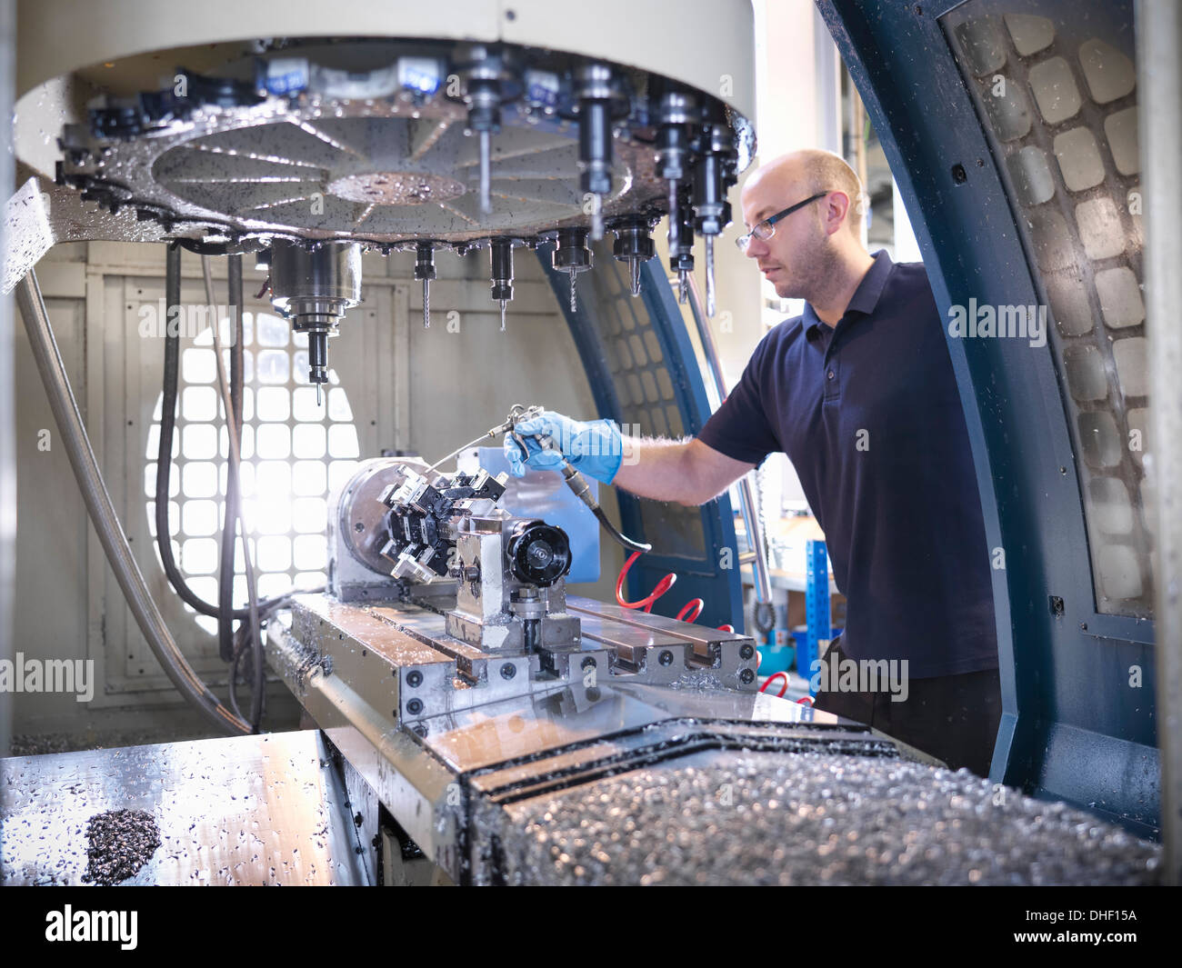 Engineer cleaning computer numerical controlled (CNC) lathe in factory - Stock Image