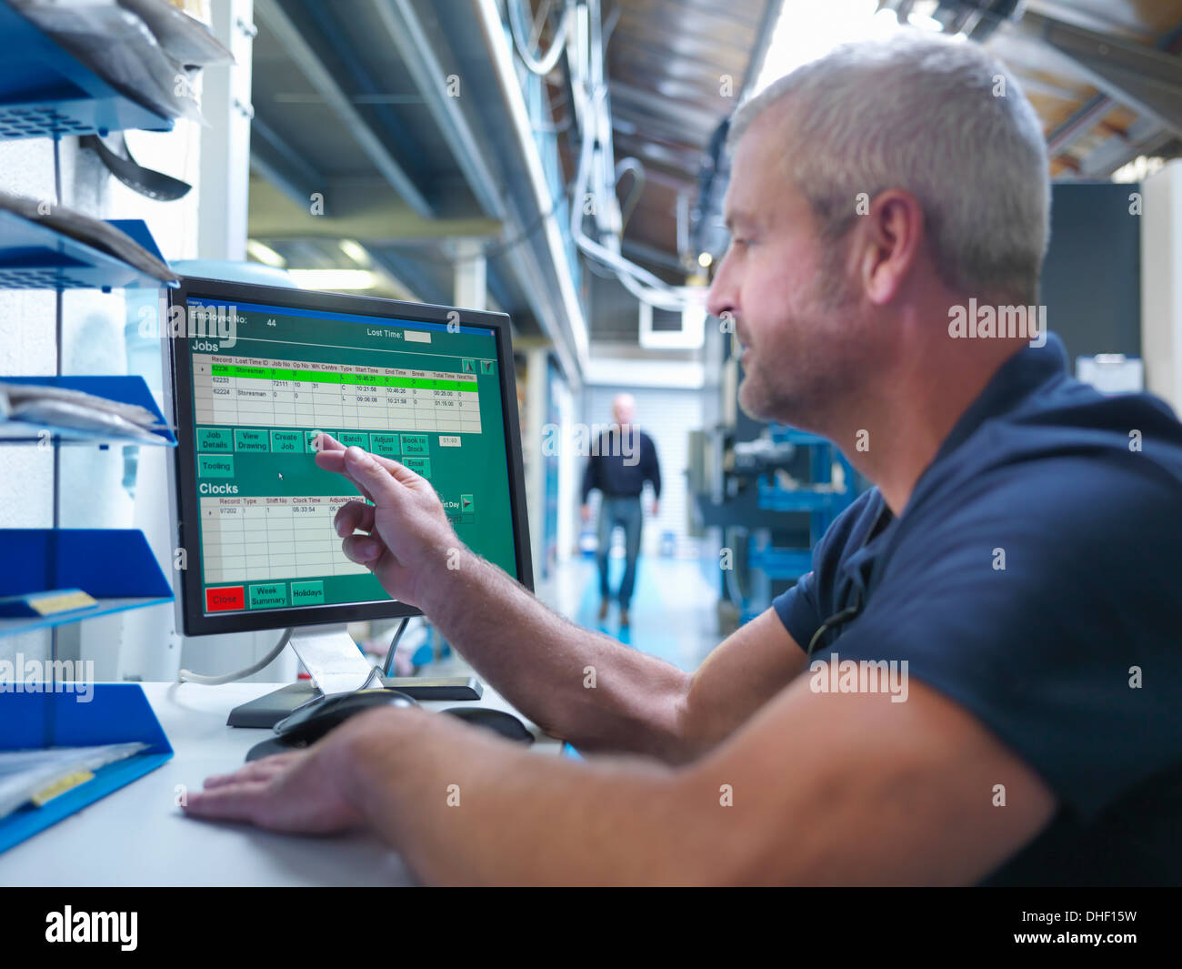 Engineer using touchscreen at computer workstation in factory - Stock Image