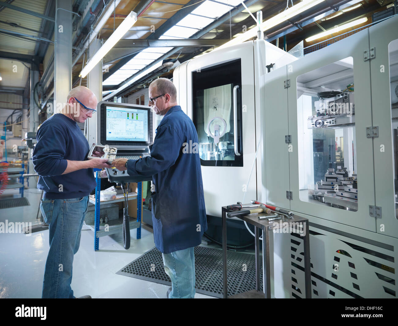 Engineers inspecting part at computer numerical controlled lathe (CNC) in factory - Stock Image