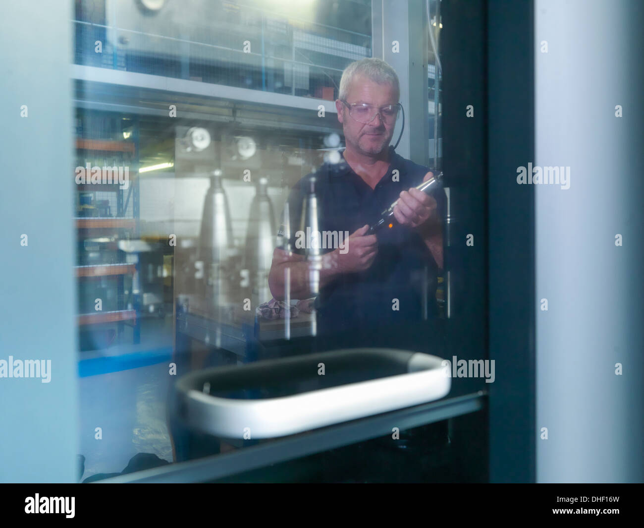 Engineer inspecting lathe cutting tool in factory - Stock Image