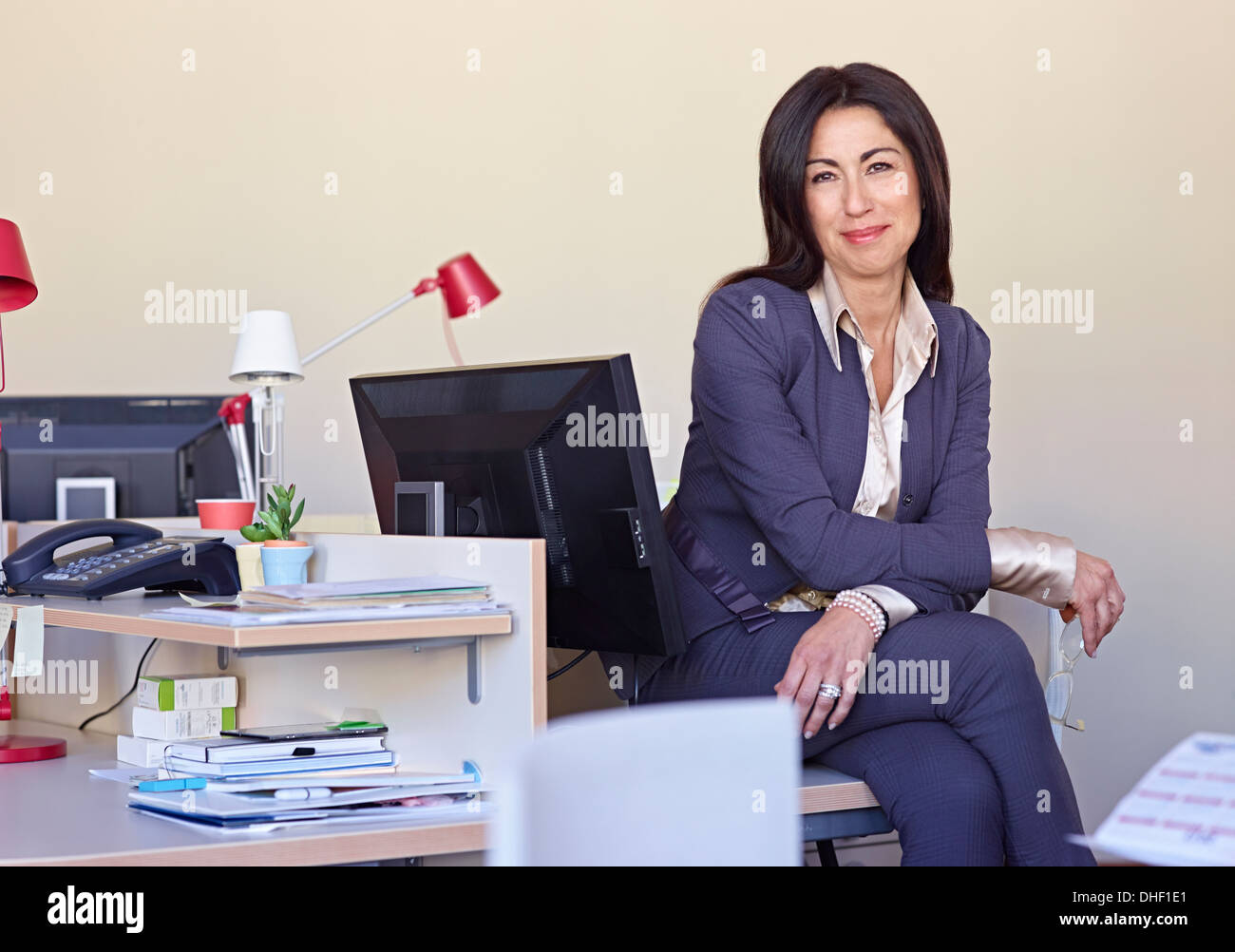Businesswoman wearing suit sitting at desk Stock Photo