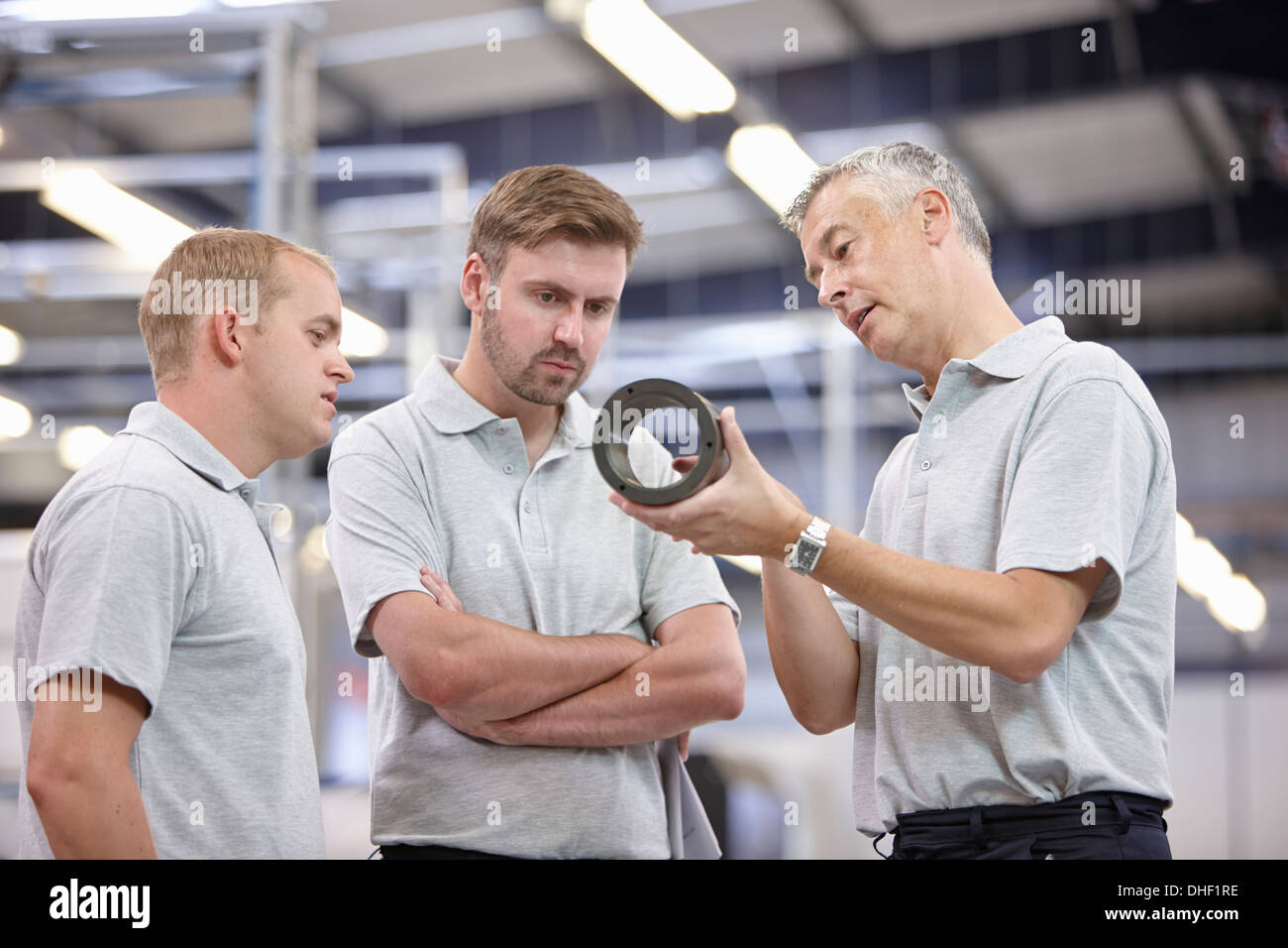 Manager discussing component in engineering factory - Stock Image