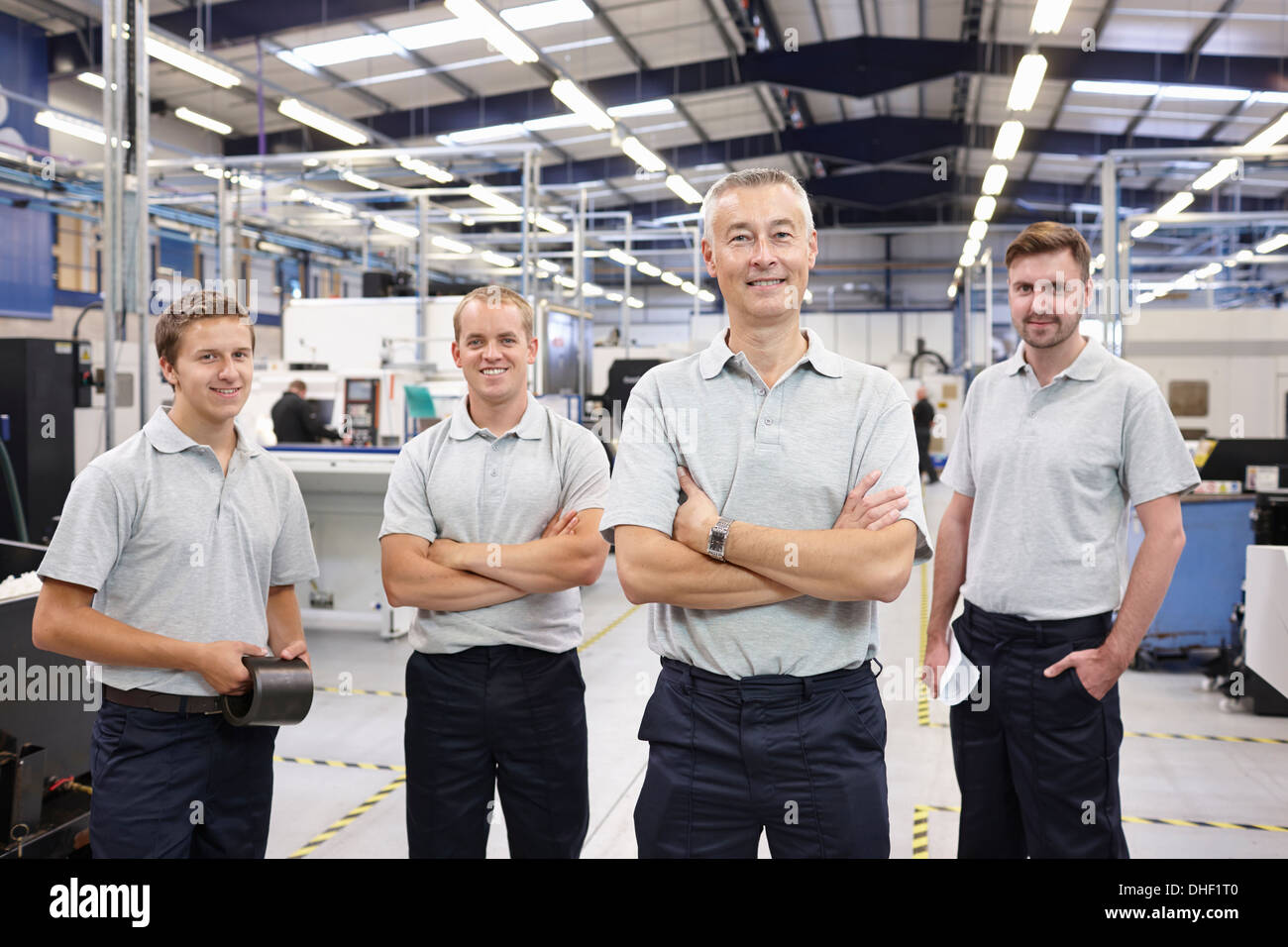 Portrait of manager and workers in engineering factory - Stock Image