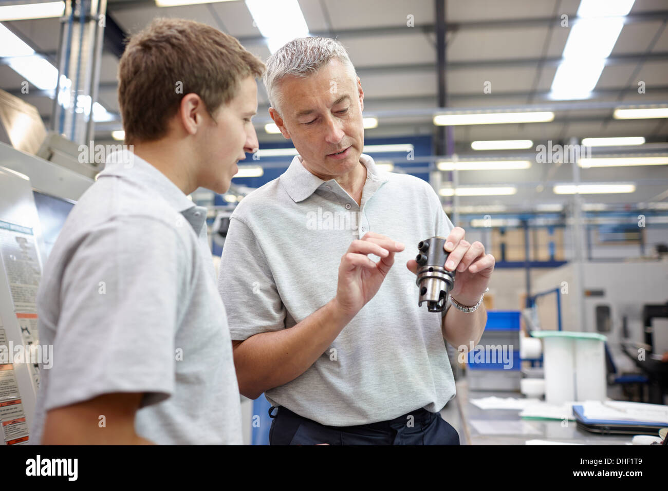 Manager and working looking at component in engineering factory - Stock Image