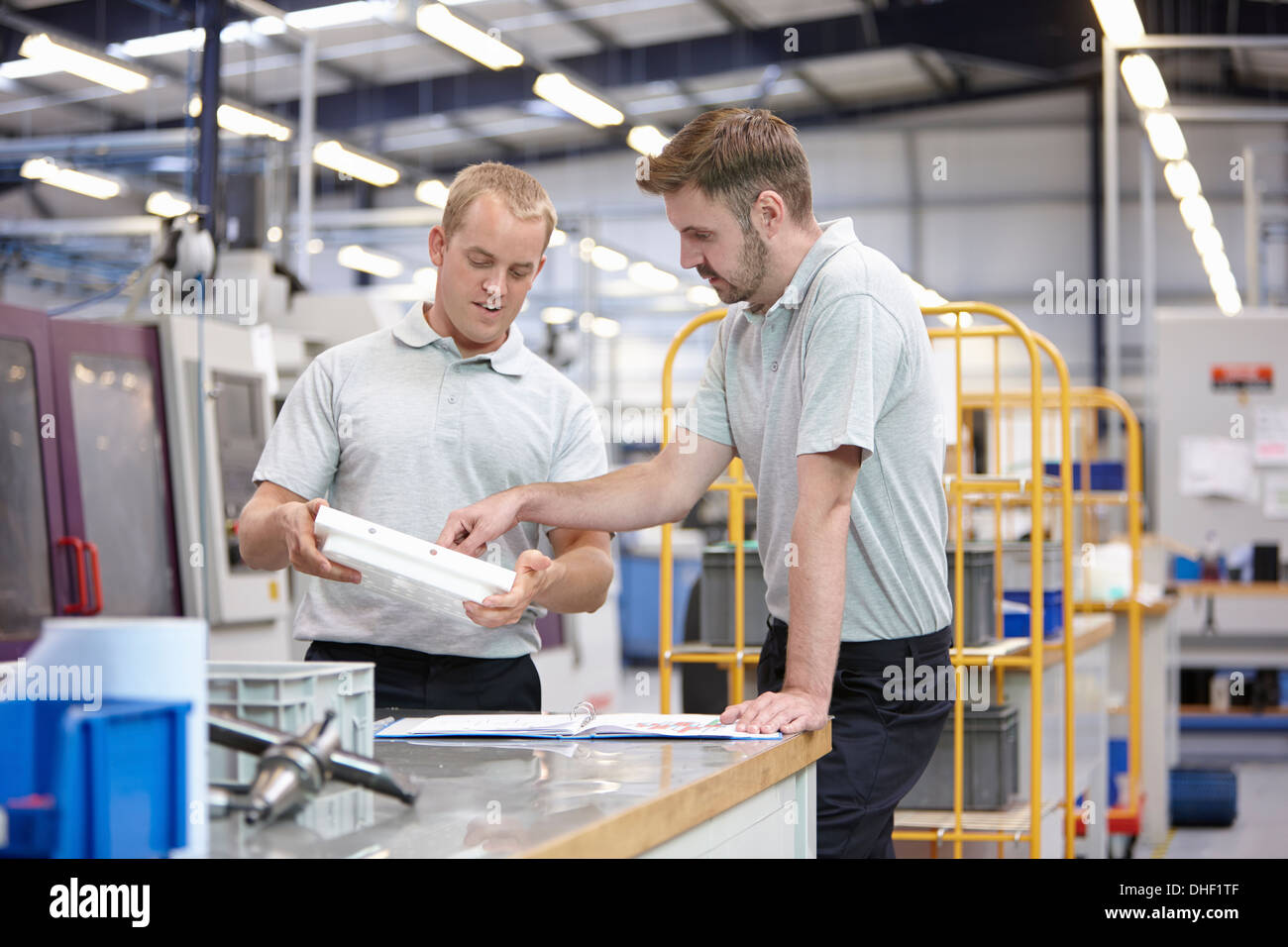 Workers discussing component in engineering factory - Stock Image