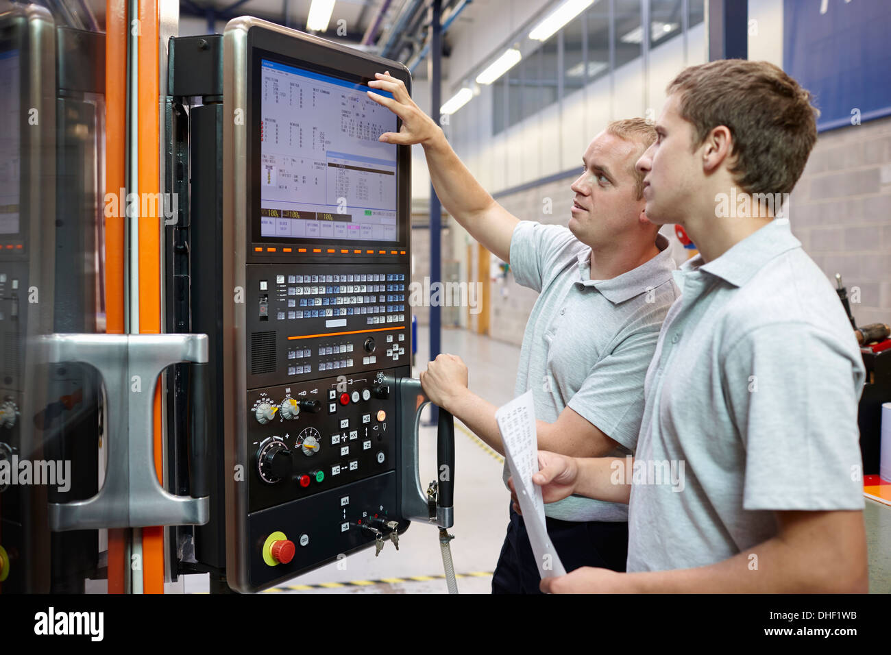 Workers looking at computer monitor in engineering factory - Stock Image