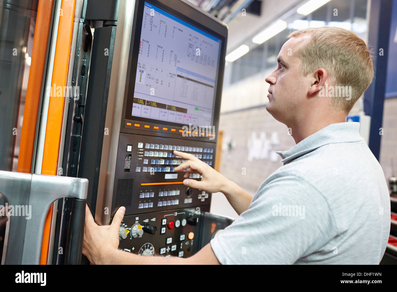 Worker looking at computer monitor in engineering factory - Stock Image