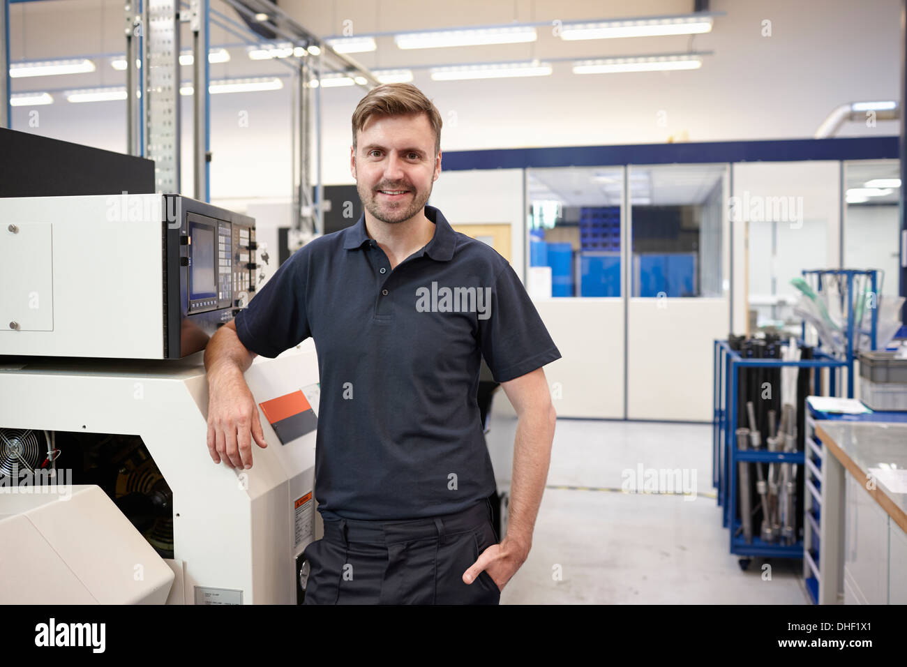 Portrait of engineer and equipment in engineering factory - Stock Image