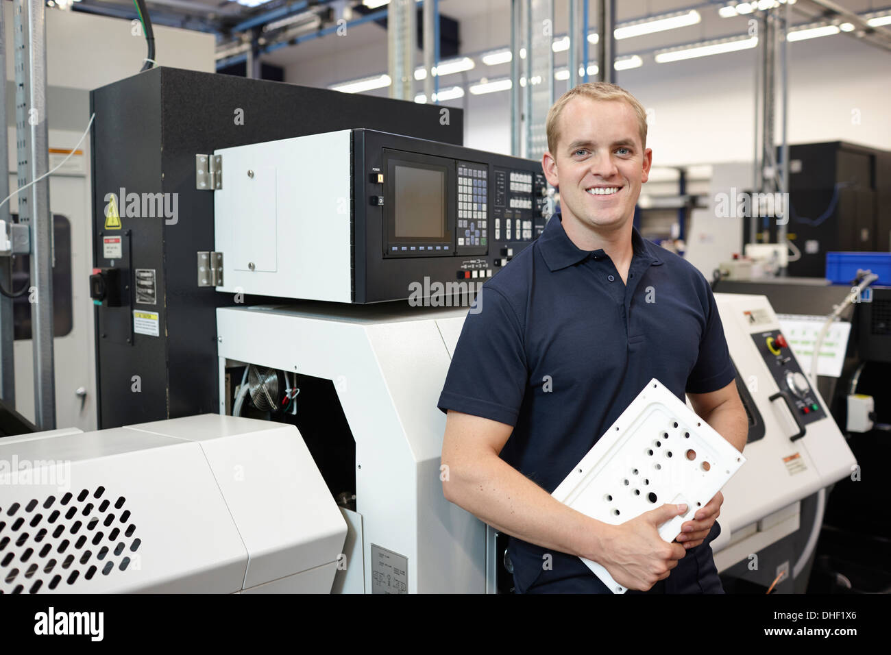 Portrait of engineer holding component in engineering factory - Stock Image