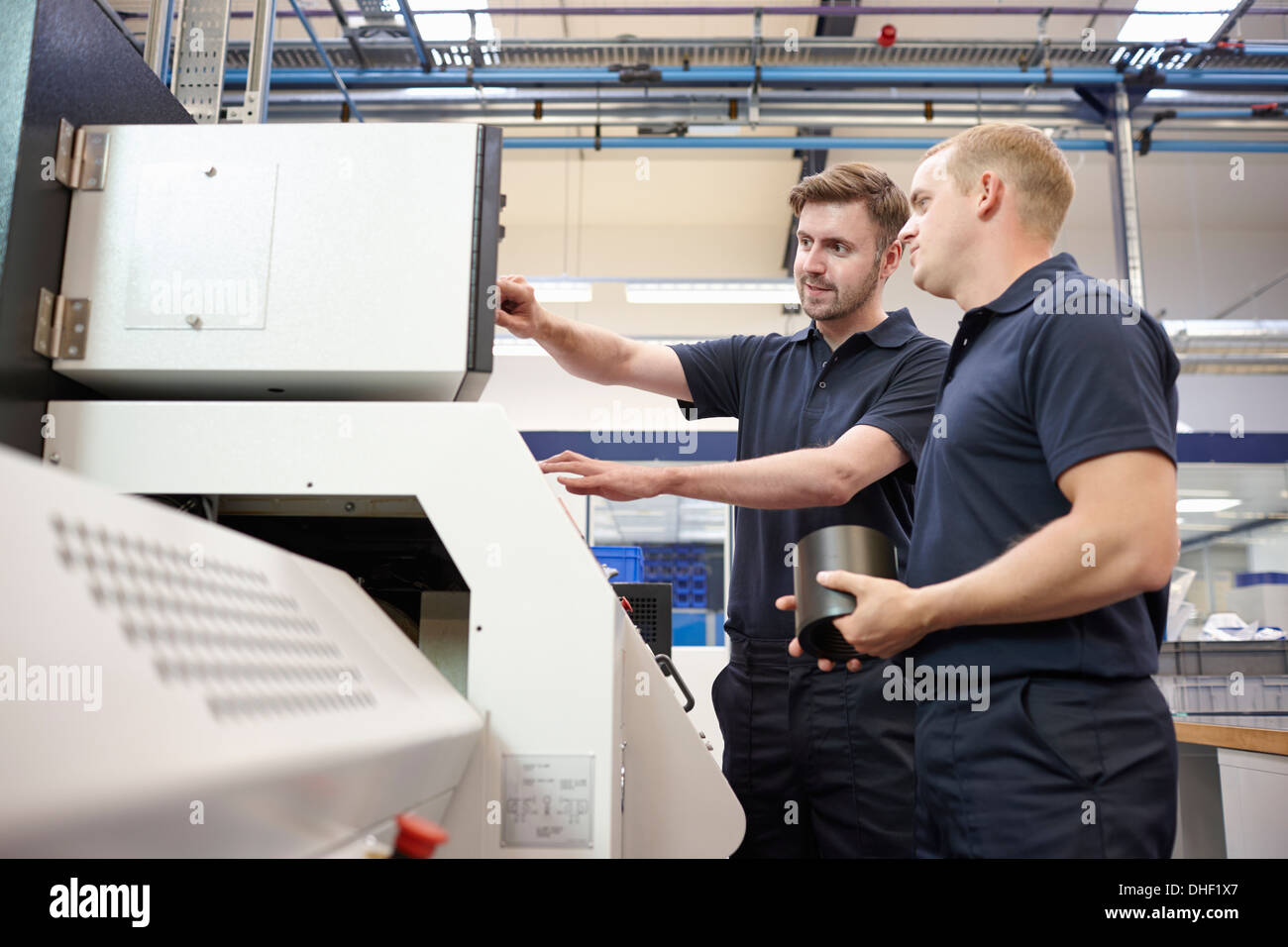 Workers checking looking at control panel in engineering factory - Stock Image