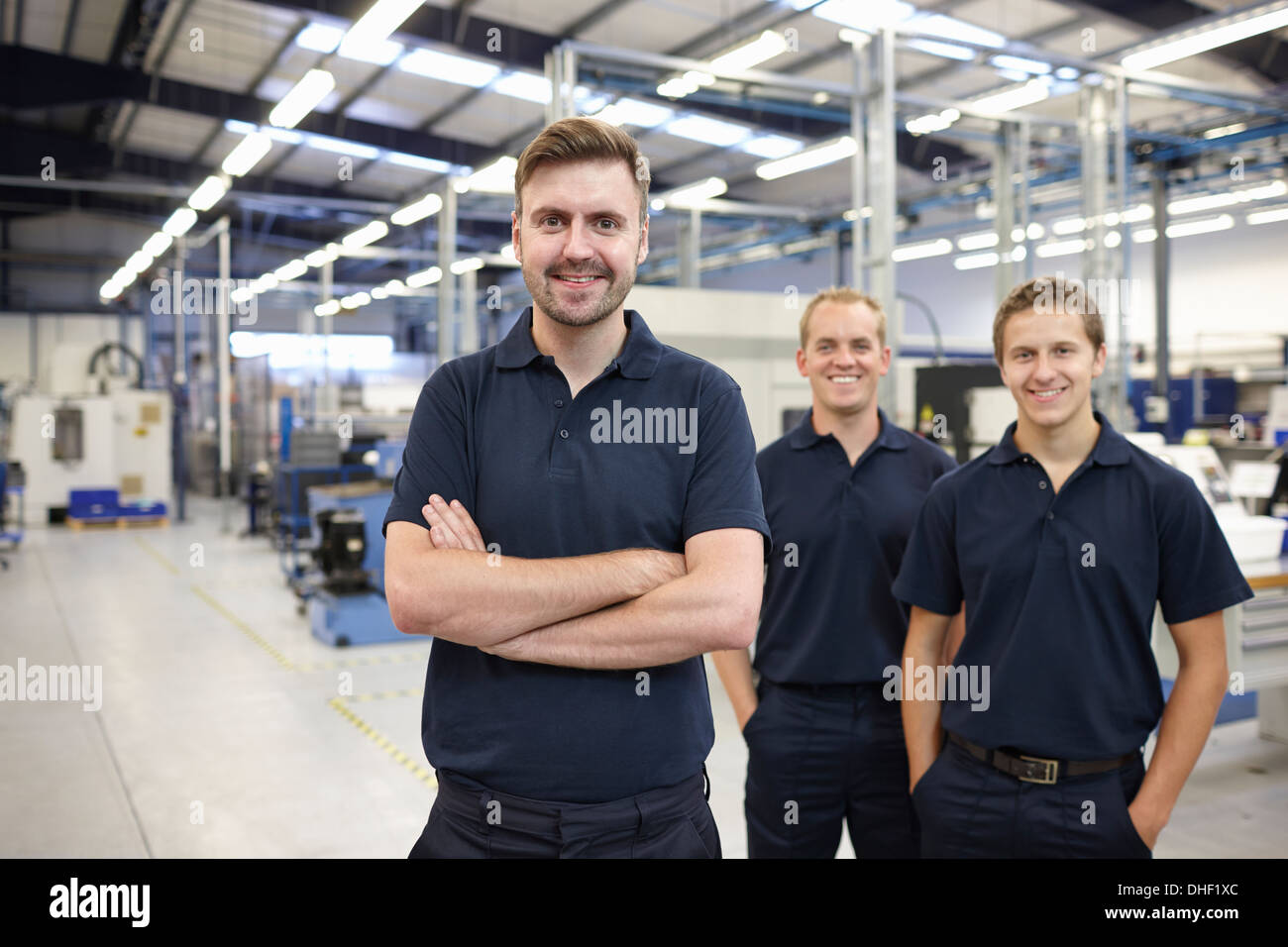 Portrait of three workers in engineering factory - Stock Image