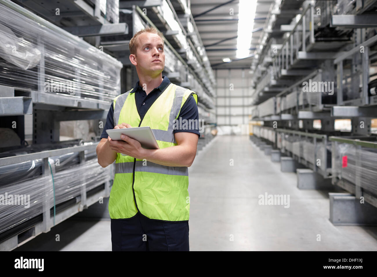 Worker checking order in engineering warehouse - Stock Image
